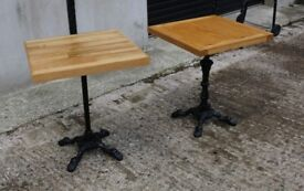 two cast iron base oak topped bar / patio tables