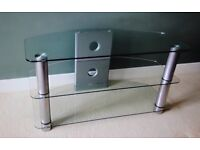 Glass TV Stand with brushed stainless steel legs and silvered back support