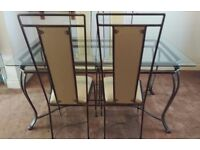 Glass topped wrought iron dining table with 4 matching high back chairs with cream leather cushions,