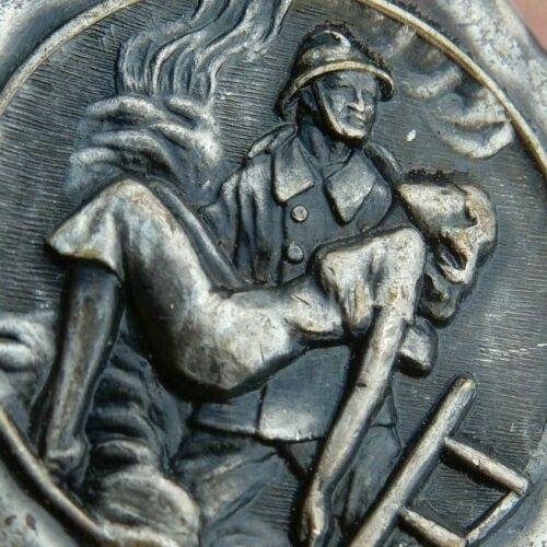 FIREMAN RESCUES GLAMOROUS GIRL  BADGE FOB 1960S ERA   33 MM DIAMETER