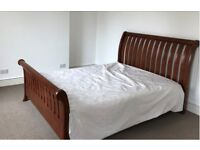 A beautiful kingsize dark hardwood sleigh bed and mattress in fantastic condition
