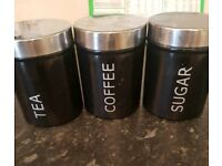 Black and silver kitchen set. Tea, coffee, sugar and biscuit tin