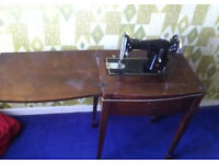 Vintage retro antique industrial sewing machine in cupboard wooden table