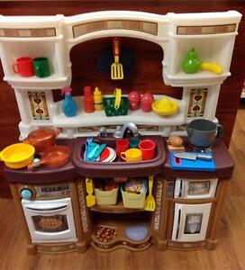 Cuisinière de marque step 2 avec aliments  et vaisselles