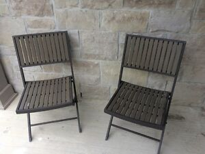 Two brown wooden and black metal frame folding chairs