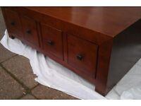 Dark wood veneer coffee table with 8 deep drawers.