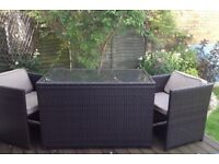 Rattan glass top table and two chairs.