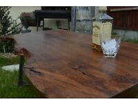 Oak wood coffee table made from live / waney edge plank and steel legs .