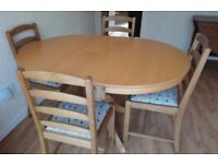 Round light oak extendable dining table and four chairs