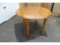 Drop-leaf yellow pine dining table and two chairs