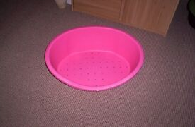a new pink plastic dog bed