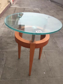 Glass table with wooden feet, in good condition. Diameter 19 in Height 24 in Lamp/occasional table