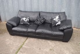 Large four seater sofa in black leather - clean - with cushions. Carlisle Ctr