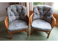 Two rattan armchairs with cushions