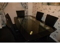 Harveys black glass dining table with 6 chairs