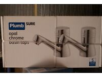 Boxed set of chrome bathroom sink taps. Brand new, unopened.