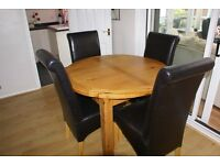 Round extending dining table and 4leather look chairs.
