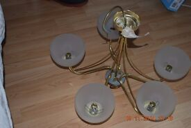 5 arm brass/gold coloured light fitting with white shades
