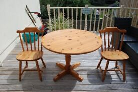A pine circular table and two chairs.