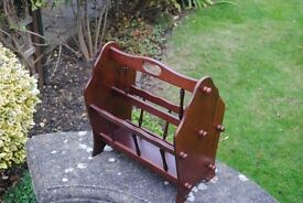 A dark wood magazine rack very attractive with spindal sides, reasonable condition.