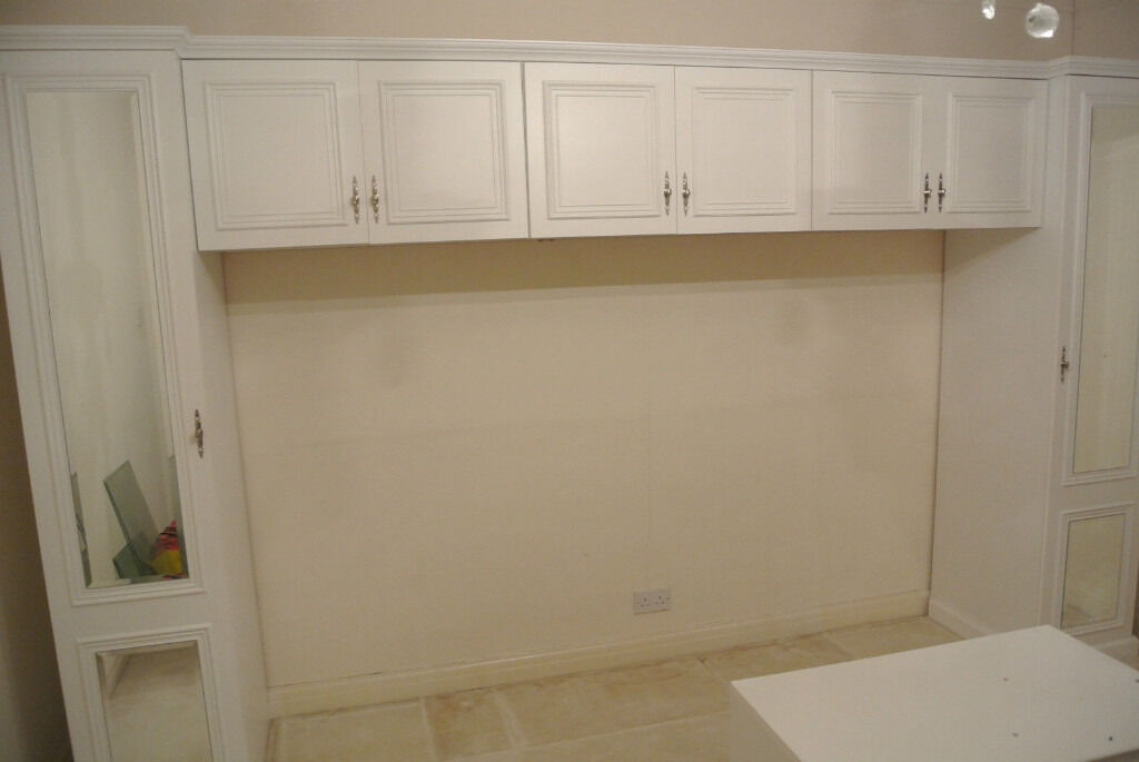 Fitted White Wardrobes Over Bed Storage Units In