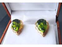 Pair of 14 karat gold and peridot stone earrings. The stones are large pear shaped baclfittinags.