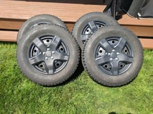 Firestone Winterforce tires on rims, with 4 wheel covers