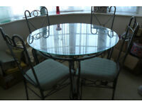 GLASS AND METAL ROUND DINING TABLE AND FOUR CHAIRS. 107cm
