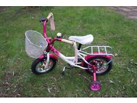 12 inch girls bike. Solid structure with stabilisers and front basket, ideal for beginner children