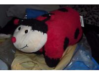 CHILDREN'S RED LADYBIRD FOLD UP CUSHION COST £20 WHEN BOUGHT AT AIRPORT