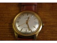 vintage timex automatic water resistant gold colored case with silvered dial leather strap