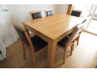 Oak effect dining room table and 6 wooden chairs with leather cushion inserts.