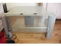 "SILVER TV UNIT WITH GLASS SHELF + GLASS LIFT UP FRONT HEIGHT 17"" LENGTH 31"""