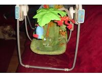 BABY SWING IN GREE JUNGLE PRINT WITH A MOBILE OVER IT WITH SOFT TOYS ON
