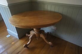 Early 1900s Oval Table with Pine Top and Walnut Base along with Metal Castors