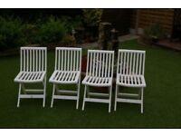 Set of four white plastic, folding garden chairs