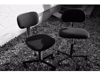 Two office-style metal and black swivel chairs