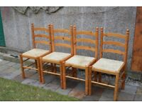 4 pine chairs, good condition, raffia seats well worn, one chair with broken stay