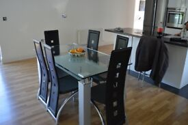 Glass table with 6 black leather seats.
