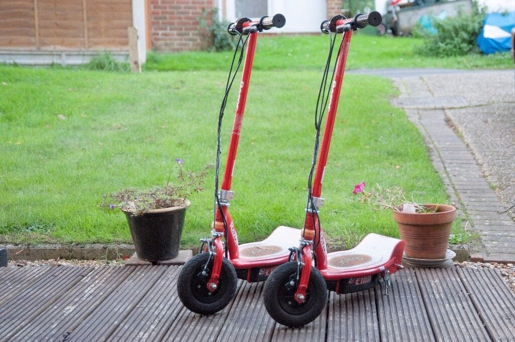 Two Razor E100 electric scooters with chargers