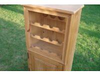 Solid rustic pine wine rack with storage cupboard below in VGC