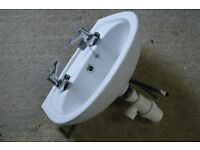 Cloakroom basin with taps and waste trap