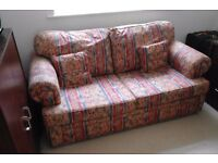 COMFORTABLE TWO SEATER SPRUNG BASE SOFA BED WITH CUSHIONS IN VERY GOOD CONDITION.