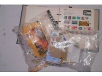 A couple of bags of used foreign stamps and a stamp folder with various foreign stamps included