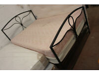 Black metal double bed frame with a mattress in a good condition