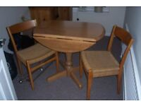 Small pine round drop leaf table and 2 ratan chairs