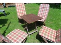FOLDING WOODEN SQUARE GARDEN TABLE AND FOUR FOLDING CHAIRS with PADDED COVERS.