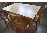 Classic, solid pine dining table with three matching chairs. Originally Ikea