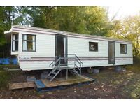 Static mobile homes off site. A pair, one with wood stove.