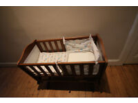 lovely wooden swinging crib with new comfortable matress and colourful bumper